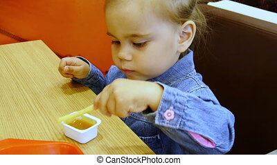 Little girl eating french fries in cafe - Little girl is...