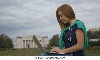 Student sitting at a laptop near the University - Girl...