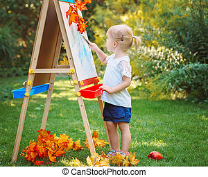 toddler girl drawing on easel