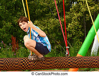 preteen happy boy in outdoor amusement park attraction log...