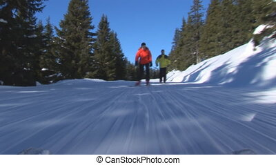 Two skiers skiing on flat slope - two skiers skiing down...