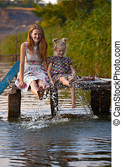 Mother and daughter sitting on the pier - smiling mother and...