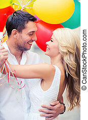 couple with colorful balloons - summer holidays, celebration...