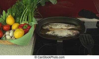 turning fried fish in pan
