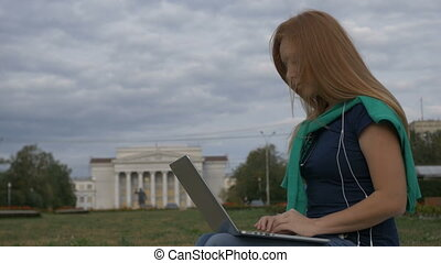 Student sitting at a laptop near the University