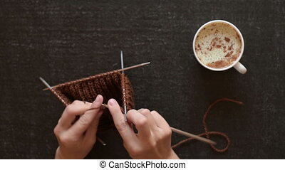 Knitting and coffee on black background - Female hands...