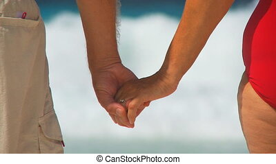 closeup seniors holding hands in front of waves