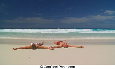 young couple stranded - young couple laying on wet beach,...