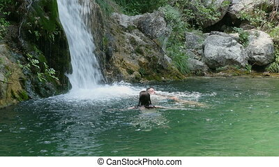 Swimming in lake with waterfall