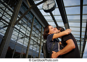 Loving couple met or parted on the platform under the clock.