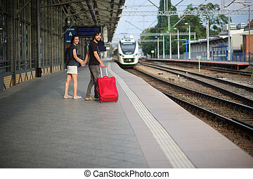 Young couple standing on the platform holding hands. - A...