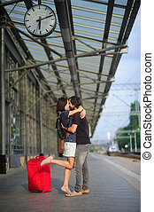 Loving couple stands on the empty platform under the clock....