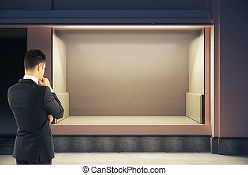 Thoughtful man looking at storefront - Thoughtful...