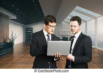Teamwork concept - Two young businessmen with laptop...