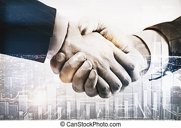Businessmen shaking hands on abstract city background with...