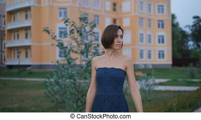 Beautiful young woman in a blue dress, goes on tratuary fun to meet her husband.