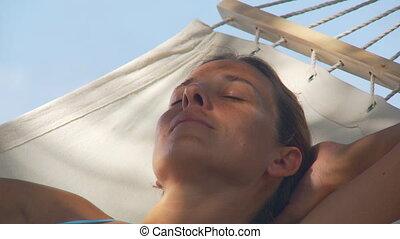 closeup of sleeping woman in hammock