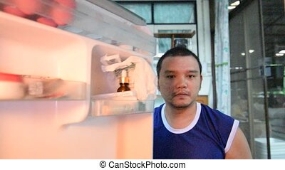 Asia man taking something from a fridge