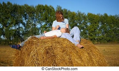 a girl with a child resting on a haystack - a beautiful girl...