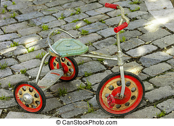 Ancient tricycle on a floor of cobbles