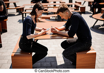 Couple looking at their smart-phones in the restaurant
