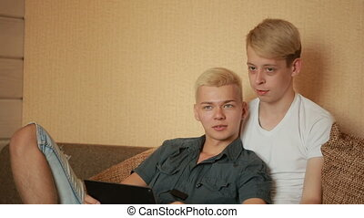 Happy gay couple using tablet in bed. gay couple. LGBT