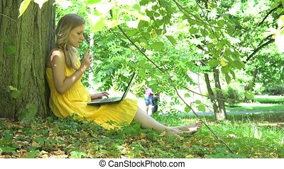 Serious woman working with laptop computer and couple walking in park on background. 4K