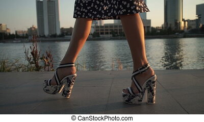 Girl walking on high heels in the evening - A young girl...