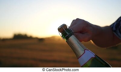 a guy opens a bottle of champagne