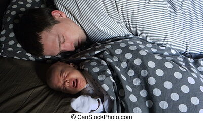 A newborn baby cries lying with his asleep father