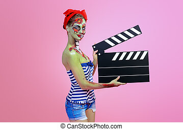 making movie - Pin-up zombie woman holding clapperboard over...