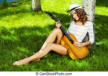 humming the melody - Romantic pretty girl sitting on a lawn...