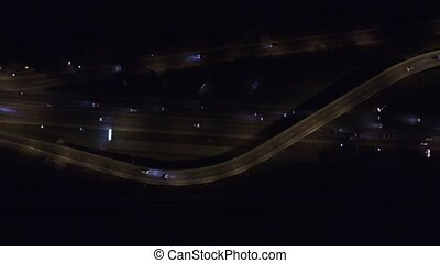 Aerial footage of highway with cars and trucks at night. -...
