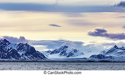 Clouds over snowy mountains and glacier in the arctic -...