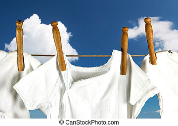 Laundry in the clouds - Baby laundry hanging on a line in...