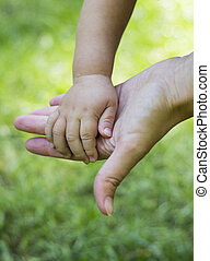 Mother holds child's hand on a background of green grass