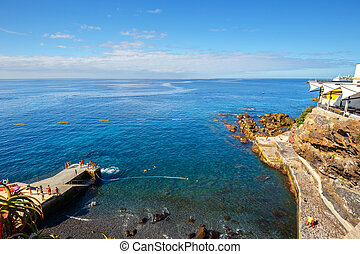 sunbathing on the city beach in Funchal, Madeira Island,...