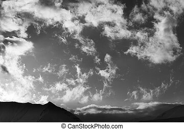 Black and white sky with clouds and mountains in evening...