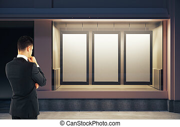 Man looking at blank posters - Back view of thoughtful...