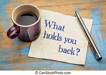 What holds you back? Handwriting on a napkin with a cup of...