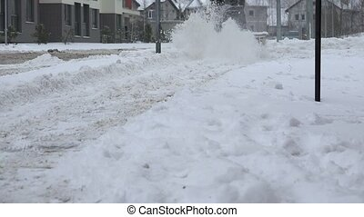 Worker cleans snow from sidewalks with snow blower machine...