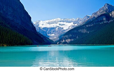 Boats in lake Louise under glacier. - Banff National Park....