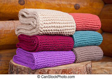 Six roll knitted scarf on wooden background.