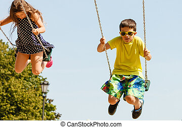 Two children having fun on swingset. - Fun and joy of...