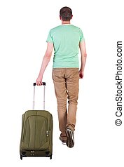 back view of walking man with suitcase. brunette guy in...