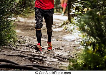 male marathon runner running in forest