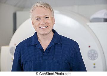 Medical Professional Smiling Against MRI Scanner - Portrait...