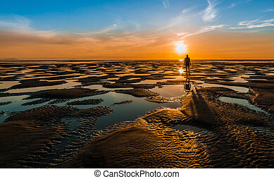 Low Tide Bach Sunset - Man standing on a beach pools area at...