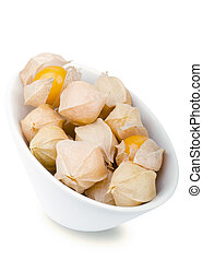 Physalis berries in white porcelain bowl over white Edible...