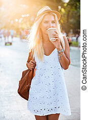 Young beautiful blonde girl drinking coffee from take away...
